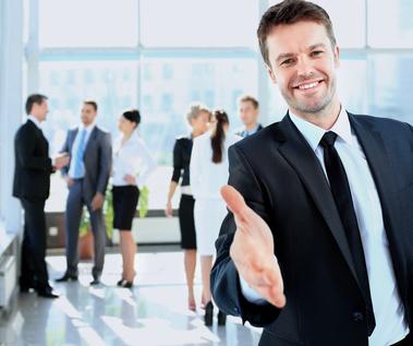 Rozmowa kwalifikacyjna - elegancko ubrany mężczyzna wyciąga rękę jakby chciał przywitać właśnie Ciebie. W tle stoją biznwsowo ubrani ludzie i rozmawiają.