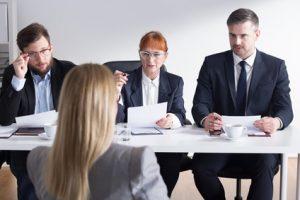 Przy stoje siedzi trzech rekruterów i jedna kandydatka. Rekruterzy przyglądają się kandydatce i zadają pytania.