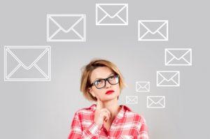 Kobieta zastanawiająca się nad tym jak pisać maile służbowe