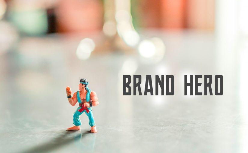"Brand hero pod postacią figurki stoi na stole, a obok jest teks ""Brand Hero"""