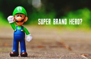 """Mała figurka Luigiego z Mariu stoi z uniesioną ręką, obok jest tekst """"Super Brand Hero?"""""""