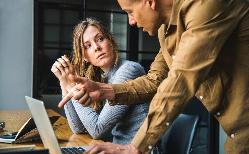 Kobieta siedzi przy biurku, na biurku stoi laptop. Patrzy z zainteresowaniem na mężczyznę, który stoi obok i tłumaczy coś na temat treści w laptopie. Scena przedstawia konstruktywną krytykę w pracy